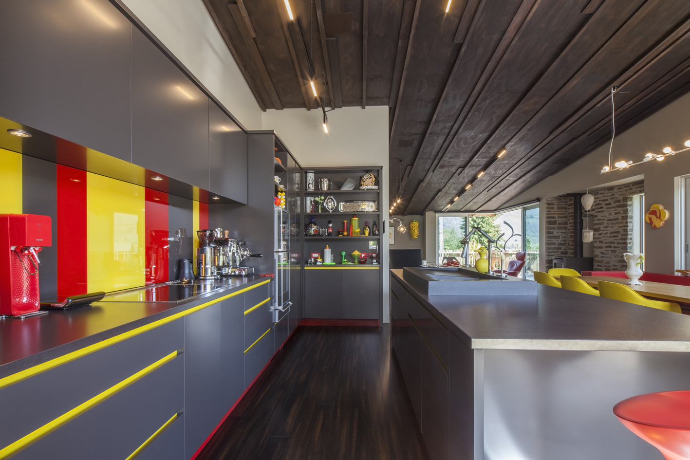 Stripy splashback -  Resene Ironsand cabinetry with accents in Resene Bullseye (red) and Resene Spotlight (yellow).  The board and batten ceiling is stained  in Resene Colorwood Dark Oak